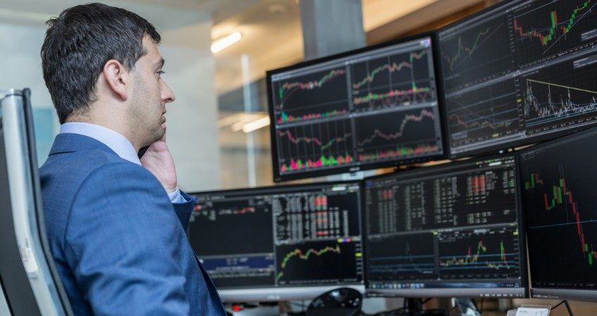 man sitting in front of computer screens looking at stock market data