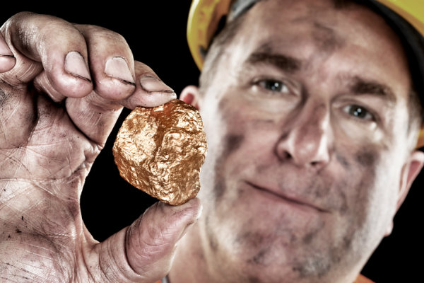 a miner shows off a gold nugget
